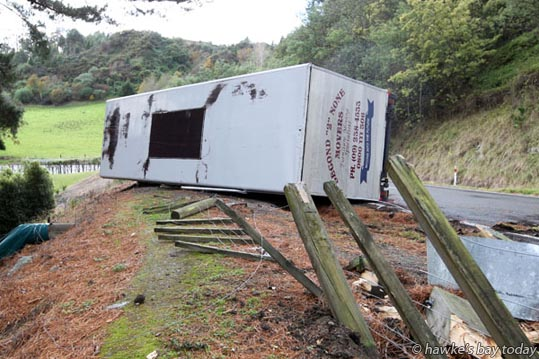Police and fire service attended an accident where a Second 2 None Movers furniture truck tipped on its side on Puketitiri Rd, Puketapu, west of Napier, destroying a steel barrier and fence, after rounding a sharp corner on a wet road. photograph
