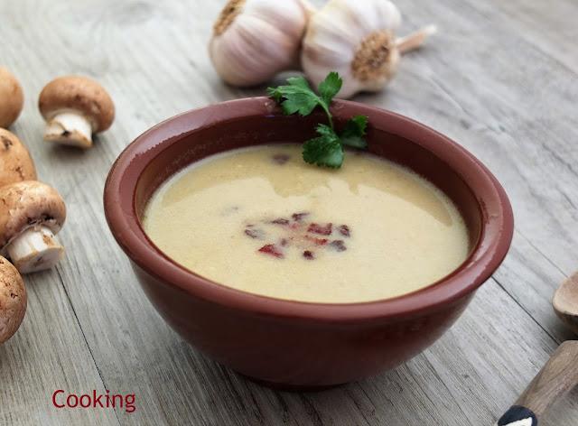 Sopa de cogumelos com alho, servida com pequenos pedaços de bacon tostado.
