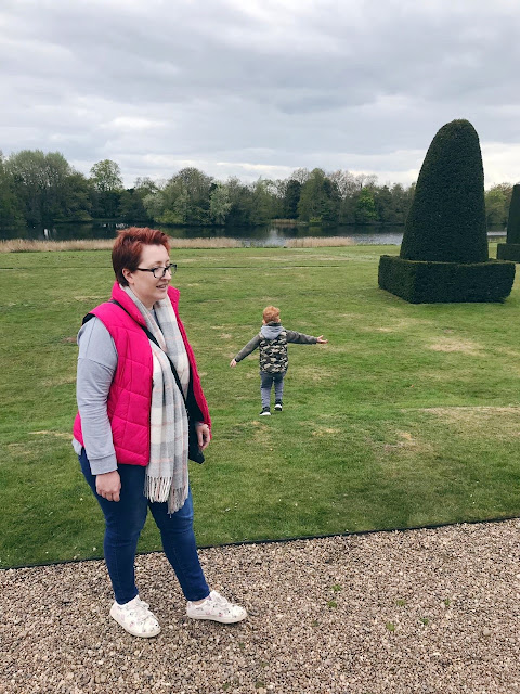 Mother at the front of a picture with a little boy running off in the background