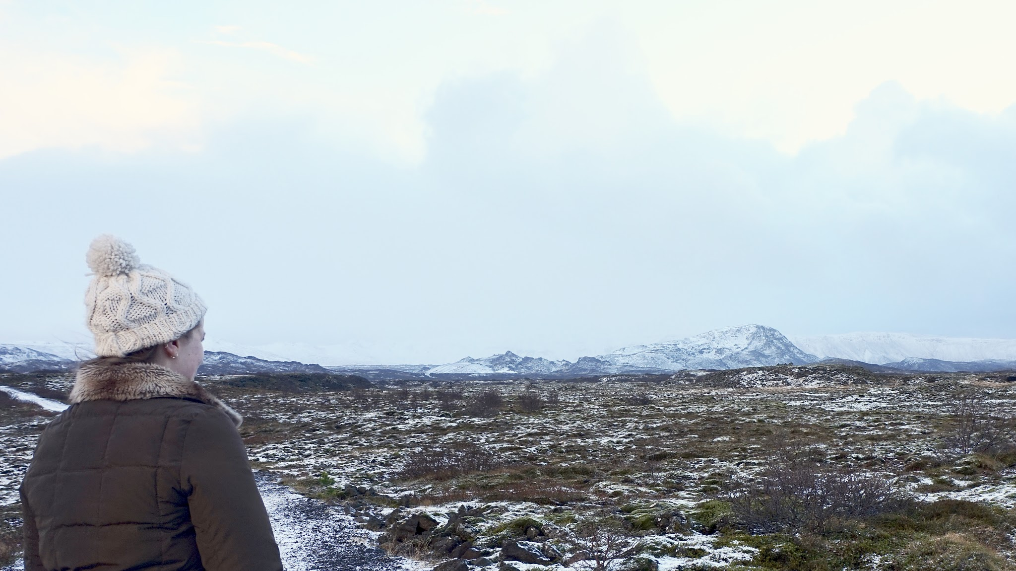 woman in bobble hat looking out onto snowy mountains