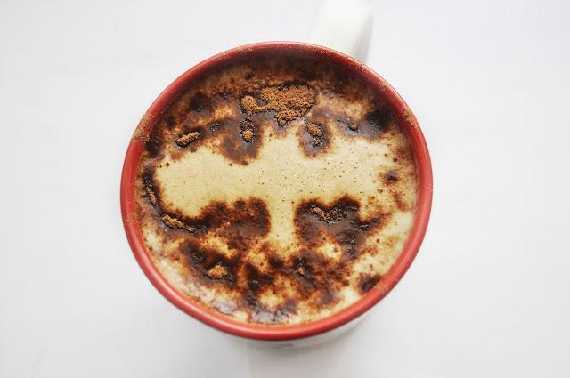 en la taza se ve un café con el logo murciélago de batman
