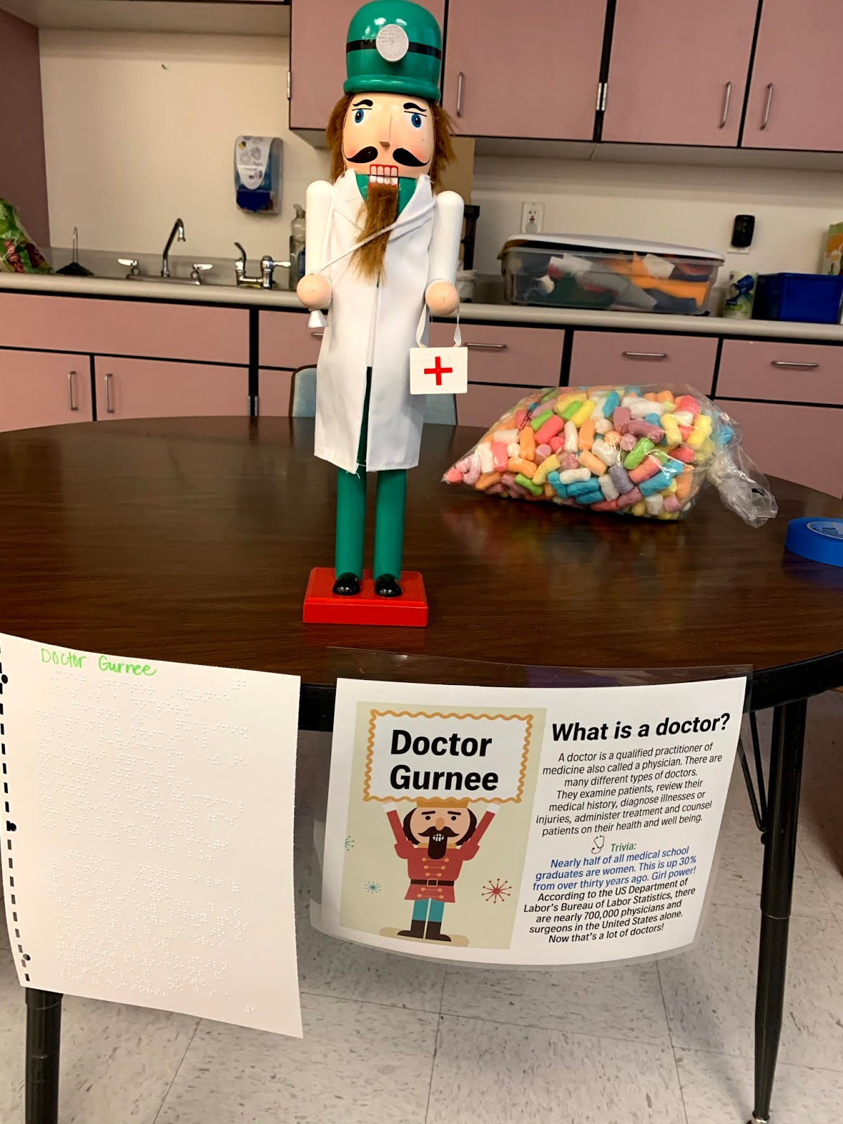 A doctor Nutcracker doll  with a game sign in Braille and print.