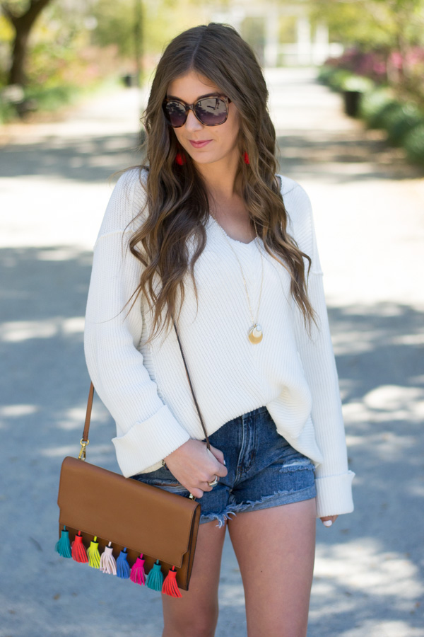 Pairing a sweater with denim shorts and wedges