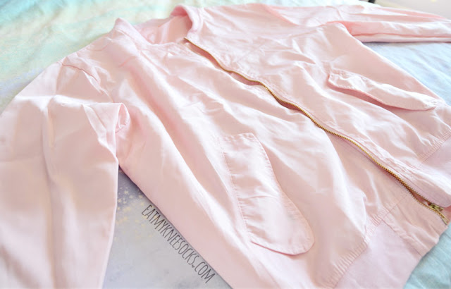 Details on the oversized pastel pink bomber jacket from SheIn, featuring front pockets and a badge/patch embellishment for a cute streetwear look.