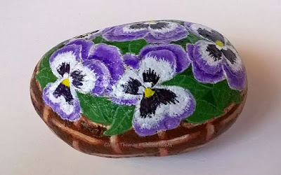 Pansies in a basket hand painted on a stone by Cindy Thomas