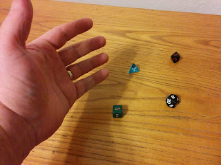 A hand hovers over the table, where several dice have just been rolled. The dice are of different varieties, including d4, d6, d8, and d10.