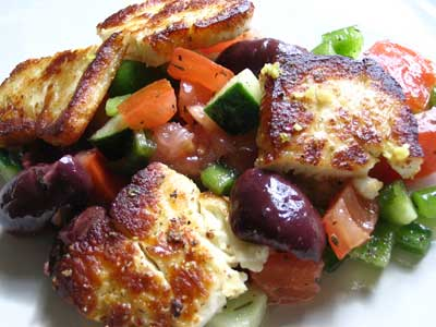 Fried Saganaki with Halloumi on a Greek Tomato Salad with Kalamata Olives