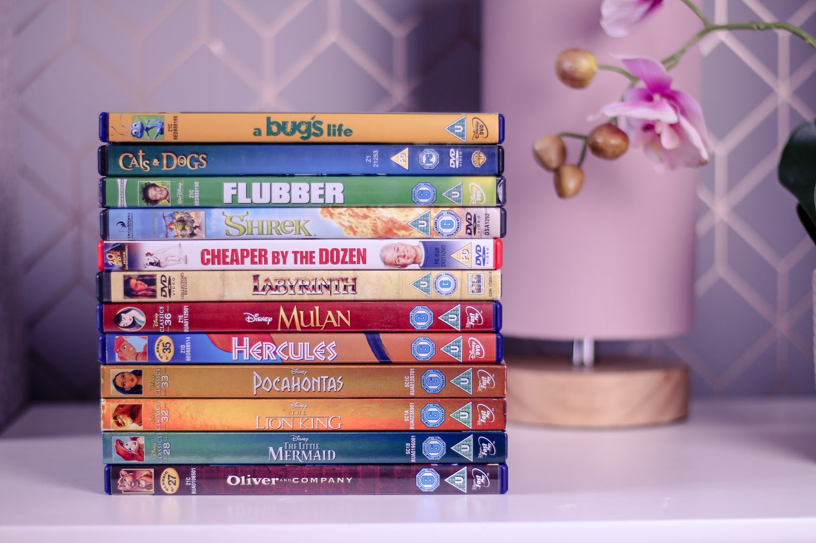 Close up photo of classic children's movies from the 90's in DVD cases such as Shrek, Flubber, Mulan, the little mermaid and more