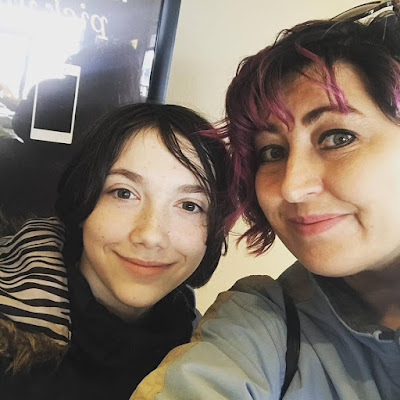 Image is of almost-13-year old Snugglebug, a female person with dark hair and green eyes, with her mother, a female person with pink hair and green eyes. They are both smiling at the camera.