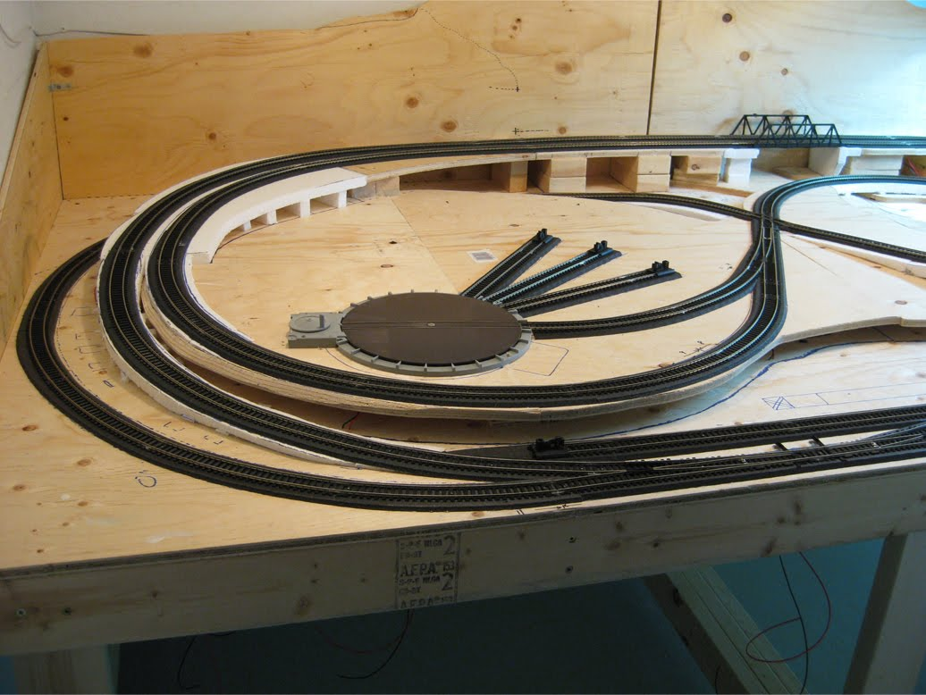 Model railroad benchwork with Atlas turn table and completed track on foam roadbed