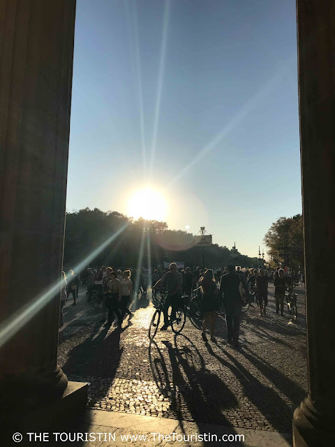 Cyclists and pedestrians and their shadows in the low-light of sunset, watched through the pillars of Brandenburg Gate.
