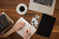 Henkilö kirjoittaa kynällä vihkoon pöydän ääressä. Pöydällä on kirjoja, silmälasit, kahvikuppi, tietokone ja vihko.a, ky