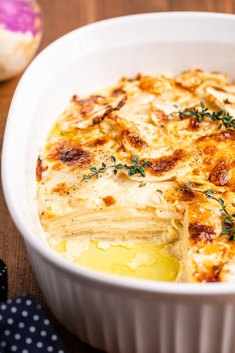 Close side view of Turnips Au Gratin in a white baking dish with a slice missing.
