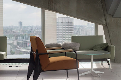 Concrete interior with angled window and midcentury curvy furniture