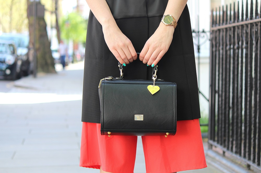 peexo fashion blogger wearing black box bag and culotte jumpsuit and sleeveless blazer in spring