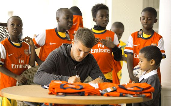 66d19438e Ligi Ndogo players looking on as Aaron Ramsey signs an Arsenal jersey.