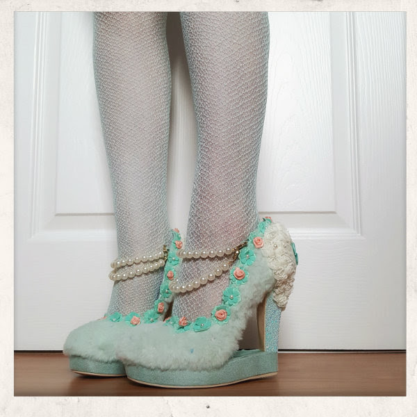 wearing Irregular Choice mint Kir Royal shoes with blue net tights