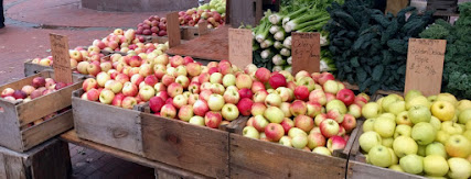 Bins filled with 6 different kinds of apples, with vegetables stacked behind them