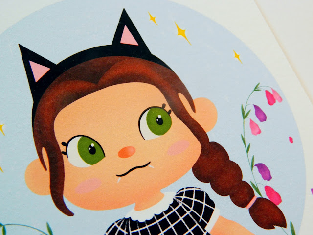 A photo showing artwork of a cute girl character wearing black cat ears