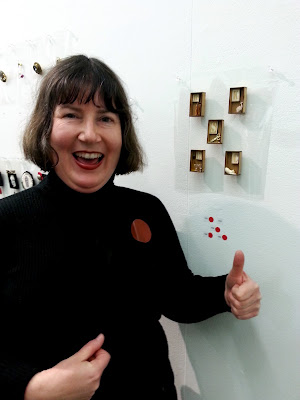 Woman looking happy and making a thumbs up sign in front of five brooches with four red dots. SHe is pointing at a red dot brooch on her jumper.