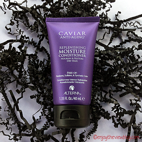 Alterna Caviar Anti-Aging Moisture Replenishing Conditioner sample tube lying on crinkled black paper strips on a white table