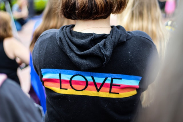 girl in pride sweater that says LOVE