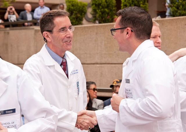 Dr. Kellermann shakes hands in a white lab coat.