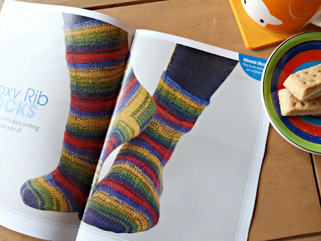 The main image of the photo is a magazine pattern picture of a pair of socks knitted in WYS Winwick Mum yarn Brightside.  There is an orange Herdy mug and a saucer with two shortbread biscuits to the right of the picture