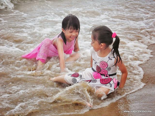 Crianças brincando na praia ao entardecer