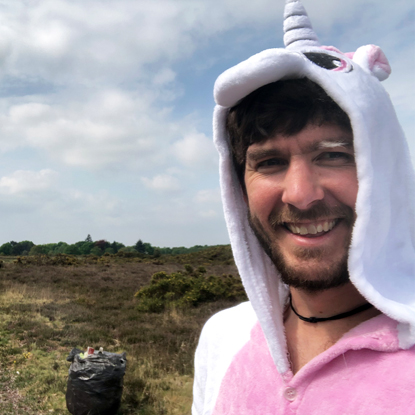 Man in white-and-pink unicorn onesie with bin bags behind him