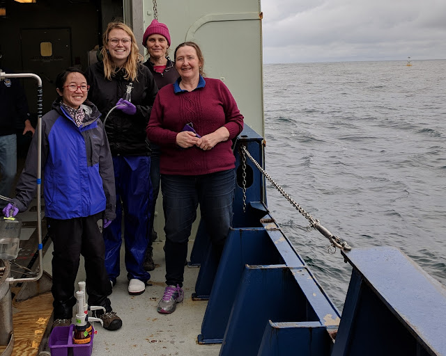 Photo of 4 smiling women standing on the deck of a research vessel. All are dressed warmly, and the second woman from the left is holding a glass bottle. To the right of the picture the open ocean is visible, and in the far background is a surface mooring which looks very small.