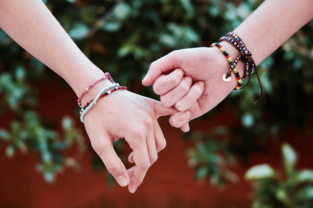 A close up of two hands interlocking their fingers while each is wearing friendship bracelets.