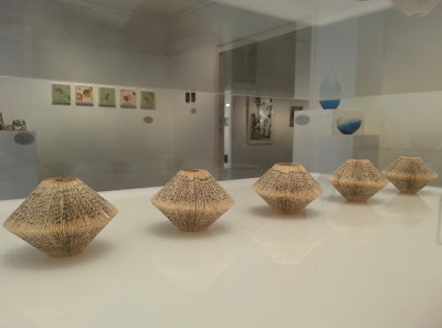 Small folded book art on display in a gallery.