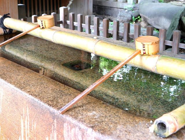 Gros plan sur des Hishaku, qui permettent de se désinfecter avant d'entrer au Temple.