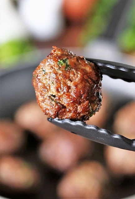 Tongs Holding Browned Homemade Meatball Image