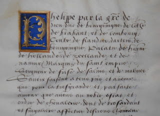 A page of handwritten text with a blue and gold initial.