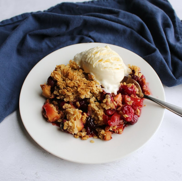serving of cranberry apple crisp on plate with scoop of vanilla ice cream