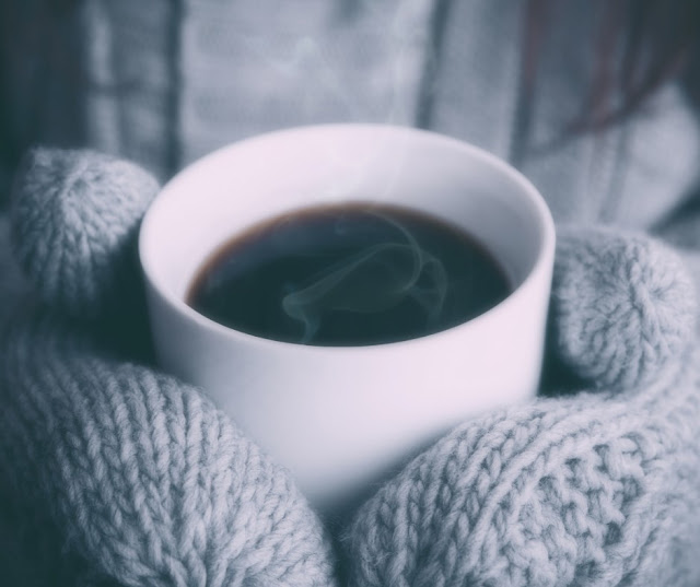 gloved hands surround a hot, steaming cup of coffee