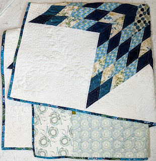 Detail of folded quilt showing parts of front, back, and binding