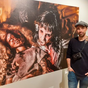 """Adrià Costa, fotoperiodista, al costat de la seva foto de gran format, cinquena entrega del cicle """"Relats fotogràfics"""". (Crèdit: Monmar Comunicació)"""