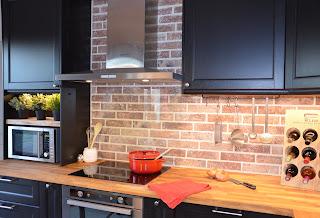 cuisine industrielle avec un plan de travail en bois brut et un mur en brique