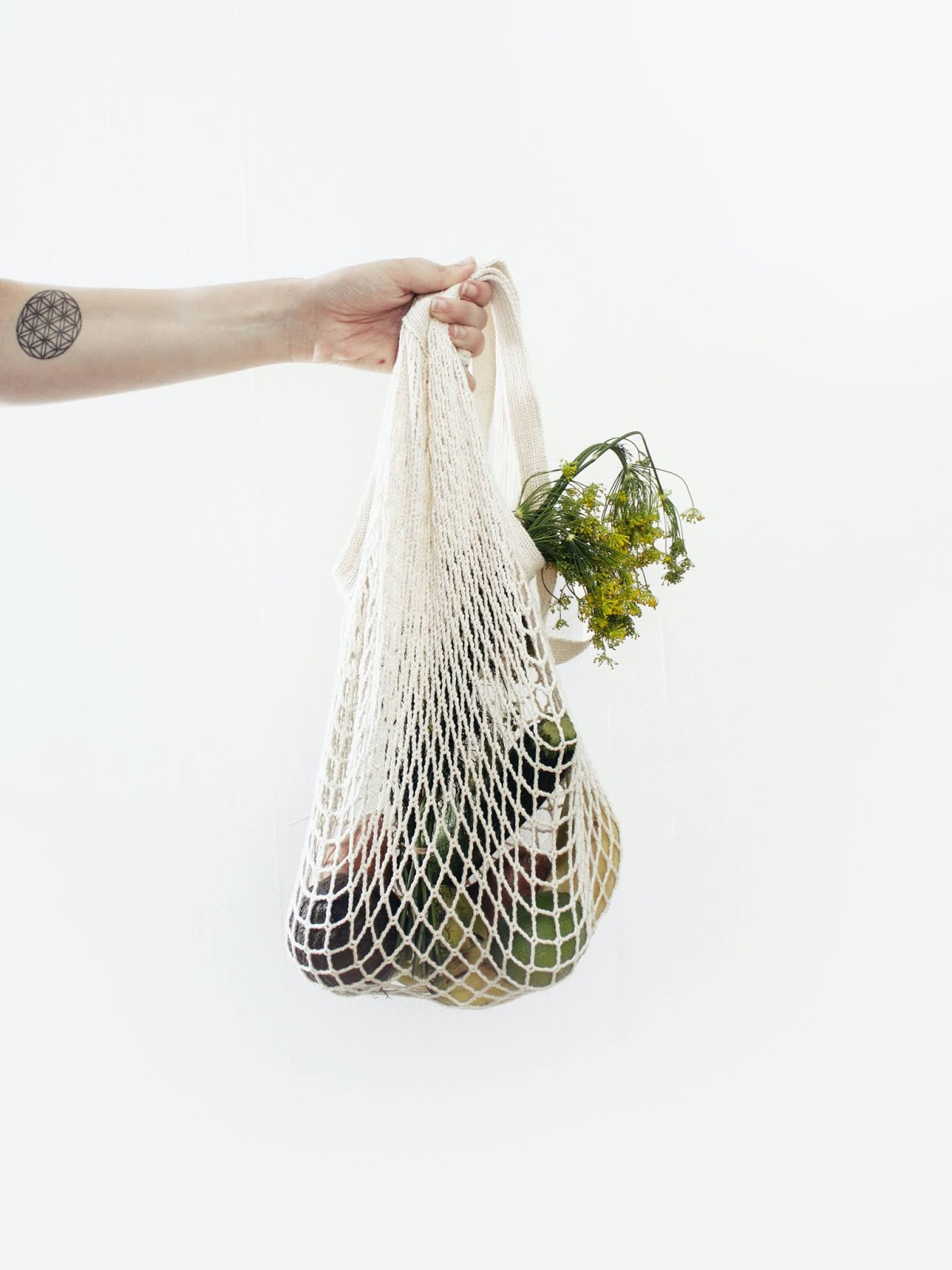 Woman holding string shopping bag with groceries