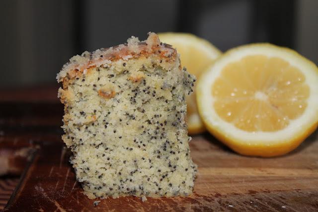 Slice Of Lemon Poppyseed Pound Cake With Lemons In Background