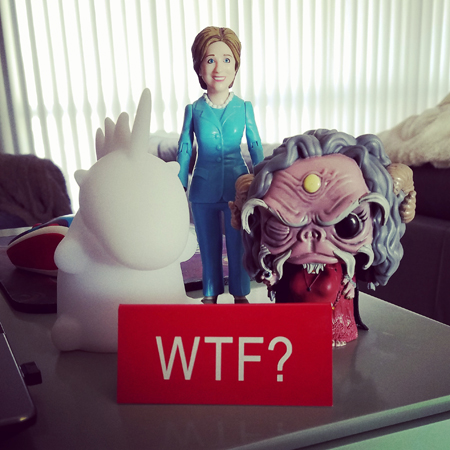 image of my desk, atop which are standing a fat unicorn lamp, a Hillary Clinton figurine, an Aughra figurine, and a deskplate reading 'WTF?'