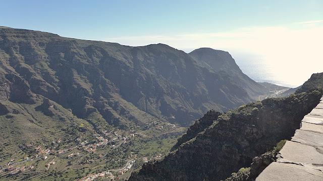 Blick in den Talkessel. Im Tal sind Häuser und Straßenzüge zu erkennen. Links und rechts erhebensich steil die grünen Berghänge. Der Atlantik und der blaue Himmel ist ebenfalls zu erkennen.