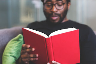 Black man wearing glasses reading a book