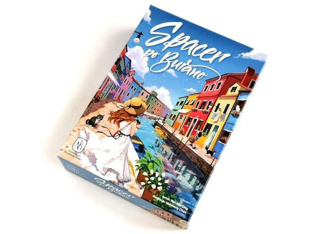na zdjęciu pudełko gry spacer po burano a na nim kanał i kolorowe kamienice, na brzegu stoi dziewczyna w kapeluszu i białej sukience a obok niej czarno biały kot