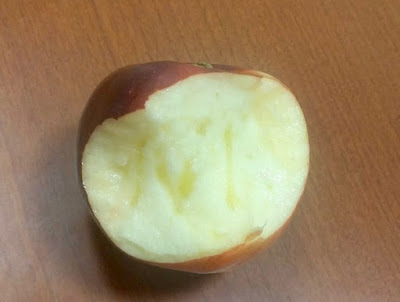 An apple with several bites taken out. The light yellow flesh has glassy yellow streaks in it.