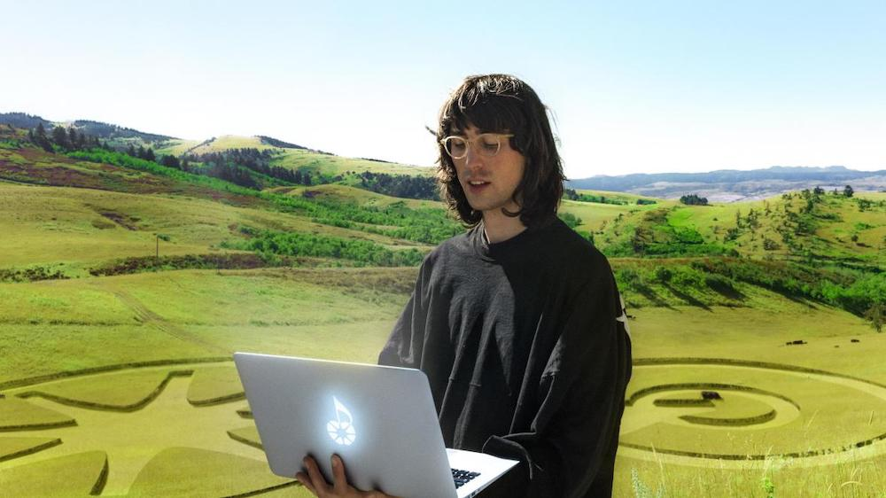 Photo of AG Cook on his laptop in a grass field