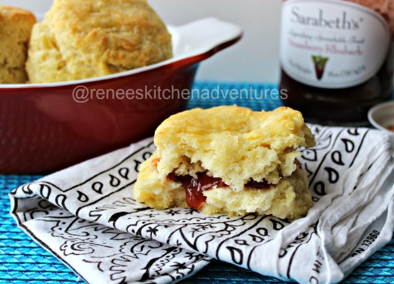 Easy Peasy Buttermilk Biscuits by Renee's Kitchen Adventures on a plate, cut open with jam in the middle. Light and fluffy looking.